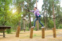 La fille est 10 années en parc s'élevant de corde raide d'aventure, la vue arrière, mode de vie actif des enfants Photographie stock libre de droits
