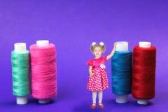 La fille est de 3 ans se tenant à côté des bobines énormes du fil sur un fond bleu Photo stock