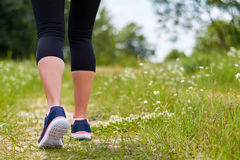 La fille est engagée dans de cardio- courses par la forêt dans des espadrilles, seulement les jambes sont évidentes, des jambes e Image libre de droits