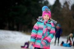 La fille est entrée dans le parc d'hiver à la commande sur le traîneau de feuille Photographie stock libre de droits