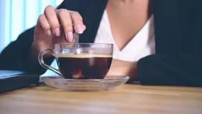 La fille est habillée dans des vêtements élégants d'affaires se reposant dans le bureau et plaçant le sucre dans le café clips vidéos