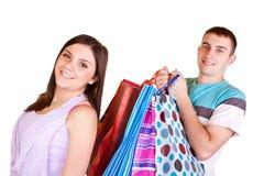 La fille est heureuse tandis que les sacs à provisions de transport d'homme photographie stock libre de droits