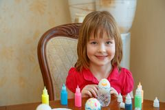 La fille est les oeufs de peinture d'amusement pour Pâques photos stock