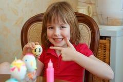 La fille est les oeufs de peinture d'amusement pour Pâques photos libres de droits