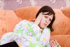 La fille est mensonge en difficulté sur le divan avec un thermomètre Photo stock