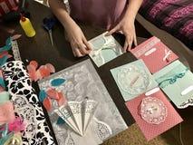 La fille est occupée à faire des cartes de voeux à la maison Utilisant le papier, la dentelle, la tresse et d'autres matériaux Photo libre de droits