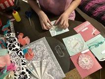 La fille est occupée à faire des cartes de voeux à la maison Utilisant le papier, la dentelle, la tresse et d'autres matériaux Image stock