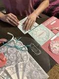 La fille est occupée à faire des cartes de voeux à la maison Utilisant le papier, la dentelle, la tresse et d'autres matériaux Image libre de droits
