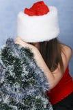 La fille est proche triste l'arbre de Noël. Image stock