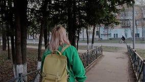 La fille est tenue sous les branches d'un arbre dans la ville et essaye d'atteindre leur juste de main dans le mouvement Elle sau banque de vidéos