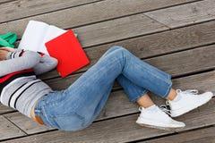 La fille est tombée endormi avec les livres ouverts sur l'étape en bois Image libre de droits