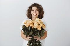 La fille est touchée avec de belles fleurs, reçues du patron Amie mignonne de brune, heureuse et déplacée avec gentil Images stock