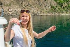 La fille est très heureuse qu'elle ait pêché un petit poisson pour l'amorce Image stock