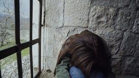 La fille est très triste derrière les barres d'une forteresse en pierre banque de vidéos