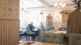 La fille et l'ami causent à une table dans un café Photographie stock libre de droits