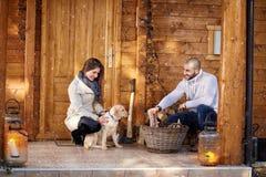 La fille et l'homme préparent le bois de chauffage Images stock