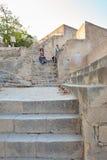 La fille et la femme s'asseyent sur le vieil escalier en pierre jaune de la chaux dans le château de Santa Barbara, Alicante, Esp Photos libres de droits