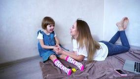 La fille et la mère affectueuses communiquent avec la petite fille et passent heureusement le temps ensemble dans la chambre pend banque de vidéos