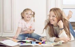 La fille et la mère s'asseyent sur le plancher et l'aspiration Image stock