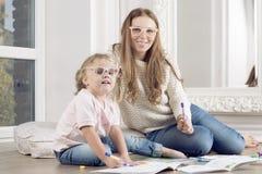 La fille et la mère s'asseyent sur le plancher et l'aspiration Photo libre de droits