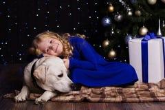 La fille et le chien à la maison se trouvent près de l'arbre de Noël Photographie stock libre de droits