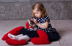 La fille et le chien heureux d'enfant d'amis jouent à la maison Photos stock