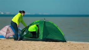 La fille et le fils de maman entrent dans la tente verte sur la plage banque de vidéos