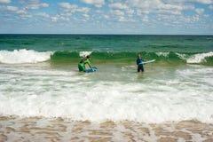 La fille et le garçon apprend à monter une planche de surf sur la mer en été Monte sur une planche de surf sur les vagues dans un images libres de droits