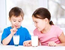 La fille et le garçon boivent du lait frais savoureux Photographie stock