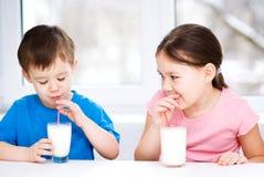 La fille et le garçon boivent du lait frais savoureux Photos libres de droits