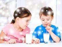 La fille et le garçon boivent du lait frais savoureux Image libre de droits