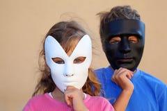 La fille et le garçon cachent des visages derrière des masques Photographie stock libre de droits