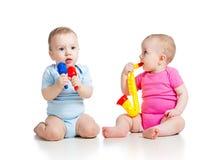 La fille et le garçon de bébés jouent les jouets musicaux photo stock