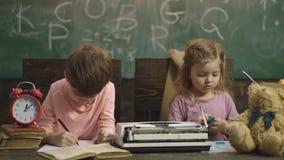La fille et le garçon dessinent dans une salle de classe d'école sur un fond de conseil pédagogique vert Retrait de fr?re et de s clips vidéos