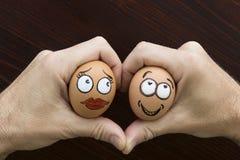 La fille et le garçon egg le visage dans la main de l'homme Photo libre de droits