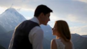 La fille et le garçon heureux avec la tendresse et amour regardent l'un l'autre le soir dans les montagnes Kazbek georgia banque de vidéos