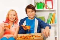La fille et le garçon heureux tiennent des morceaux de pizza sur le sofa blanc Image stock