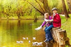 La fille et le garçon mignons jouent avec les bateaux de papier sur l'étang Photos libres de droits