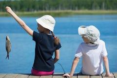 La fille et le garçon ont pêché les poissons sur la rivière Image libre de droits