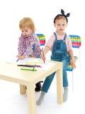 La fille et le garçon s'asseyant à la table dessinent Images libres de droits