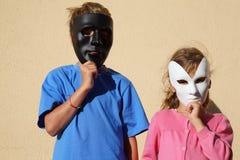 La fille et le garçon s'usent des masques et regardent l'appareil-photo Image libre de droits