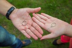La fille et le garçon tiennent l'anneau dans des vos mains sur le fond vert Histoire d'amour Photo stock