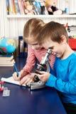 La fille et le garçon utilise un microscope et écrit des résultats Photo stock
