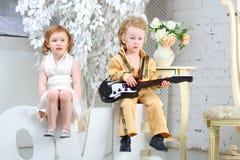 La fille et le musicien de bruit avec la guitare s'asseyent sur des lettres Images stock