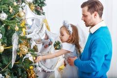 La fille et le père décorent l'arbre de Noël Photographie stock