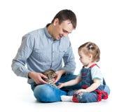 La fille et le père d'enfant jouent avec le chaton de chat Images stock