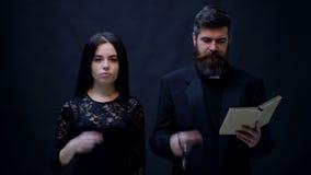 La fille et le prêtre sont baptisés sur un fond noir Partie de Halloween et concept de célébration banque de vidéos