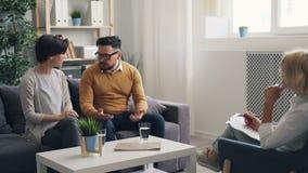 La fille et le type des couples mariés combattant pendant la consultation tandis qu'écoute de docteur banque de vidéos