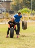 La fille et le type jettent le pneu Images stock