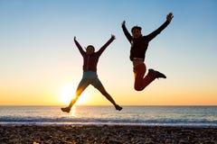 La fille et le type sautant haut avec des bras lèvent le lever de soleil spectaculaire à la côte d'océan Photographie stock